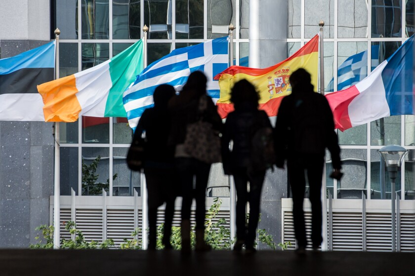 Pedestrians are silhouetted against the flags outside the European Parliament in Brussels. Despite eight countries' pending applications to join the 28-member European Union, no new additions are expected in the foreseeable future.