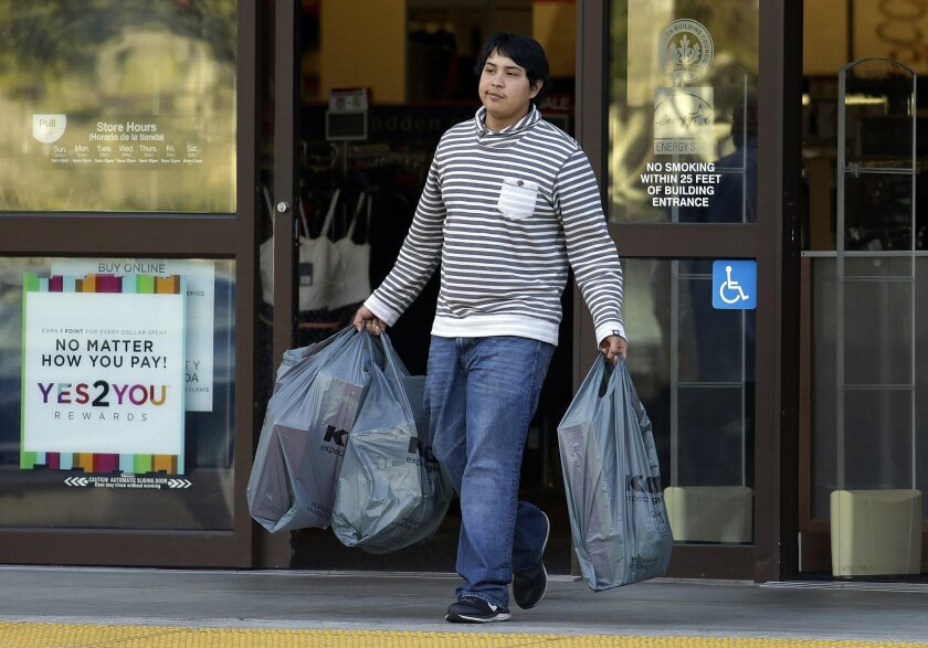 FILE - In this Dec. 17, 2015 file photo, a man carries bags out of a department store, in Alameda, Calif. U.S. consumer spending rebounded in November after a weak showing in October, while a key inflation gauge posted the fastest year-over-year increase in 11 months. The Commerce Department said W
