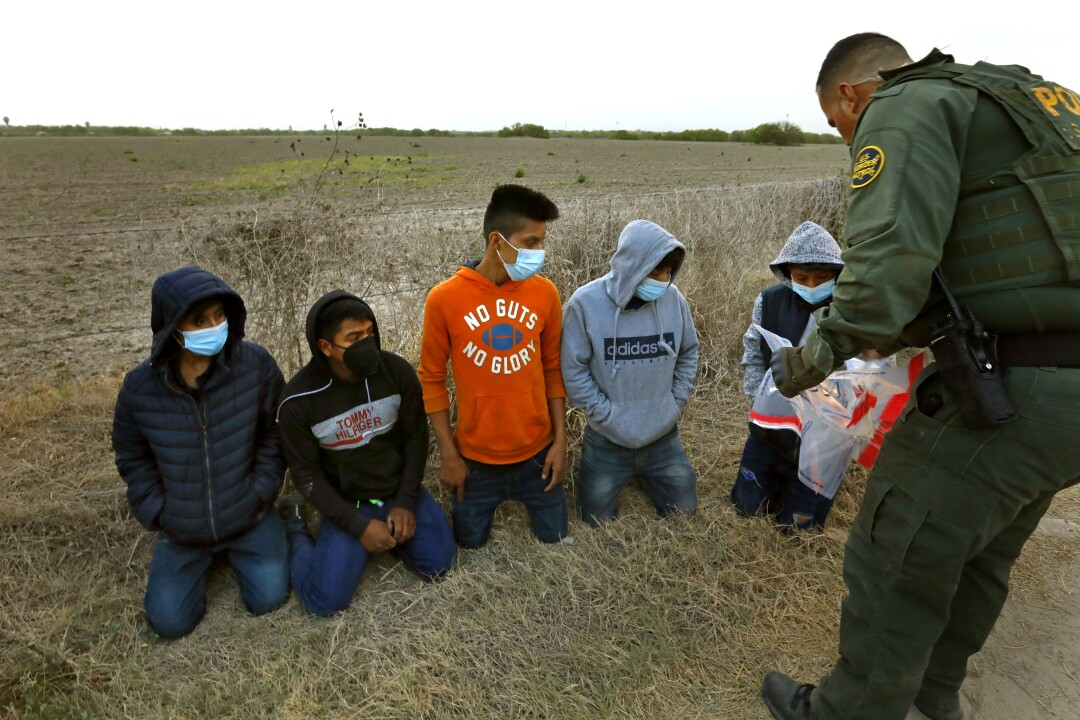 Young migrants on their knees in front of a border agent