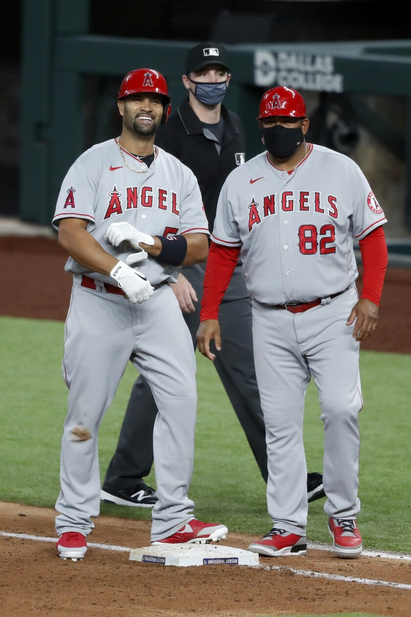 Angels' Albert Pujols stands by first-base coach Jose Molina smiling.