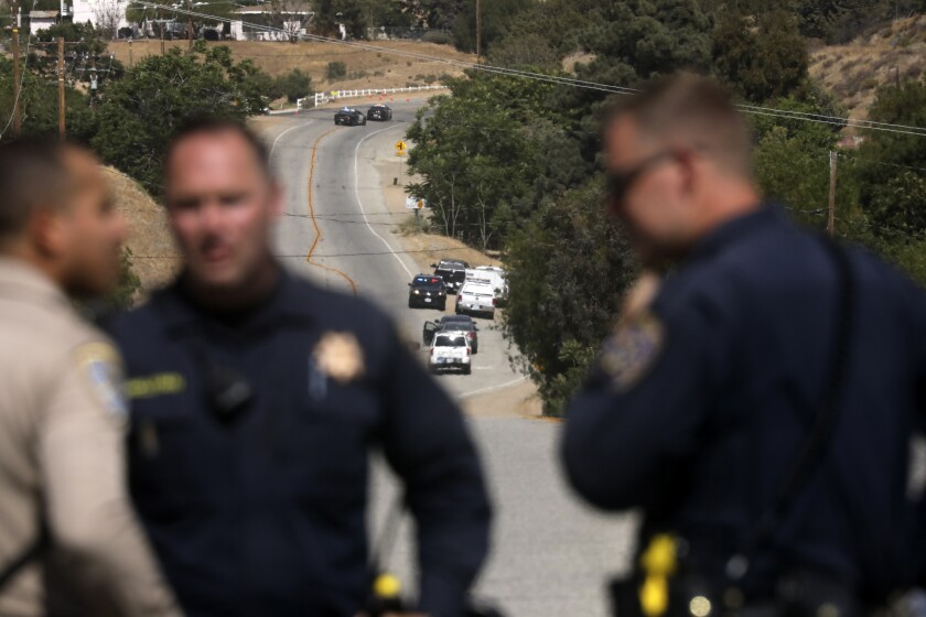 Law enforcement authorities close off a road during an investigation for a shooting at fire station 81 in Santa Clarita, Calif. on Tuesday, June 1, 2021. An off-duty Los Angeles County firefighter fatally shot a fellow firefighter and wounded another at their fire station Tuesday before barricading himself at his home nearby, where a fire erupted and he was later found dead, authorities said. (AP Photo/David Swanson)