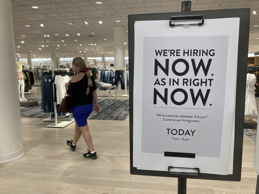 A customer walks behind a sign at a Nordstrom store seeking employees, Friday, May 21, 2021, in Coral Gables, Fla. The number of Americans seeking unemployment benefits dropped last week to 406,000, a new pandemic low and more evidence that the job market is strengthening as the virus wanes and economy further reopens. (AP Photo/Marta Lavandier)