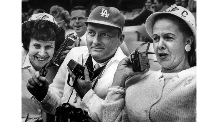June 2, 1965: Dodgers Booster club members Gladys Fuqua, left, Rolfe Larsen, center, and Vangie Scoler listen to Vin Scully.