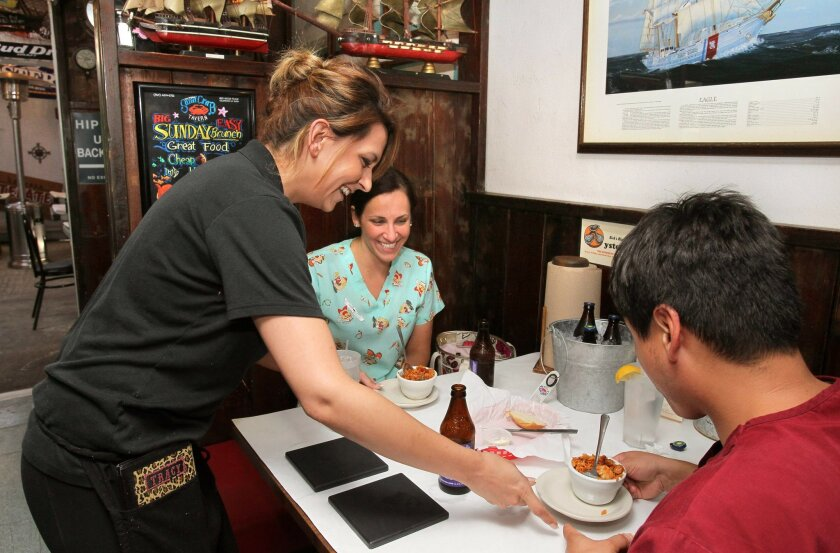 At The Original Sand Crab Tavern waitress Tracy Ryan serves Jambalaya soup to customers Sarena Terrazas and Daniel Rocha. The place is in an area of light industrial buildings in Escondido.