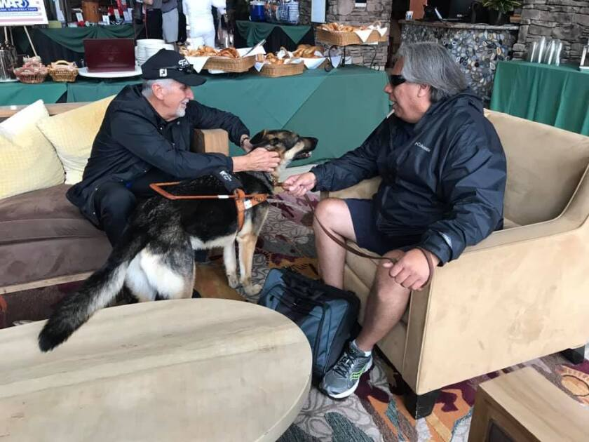 Craig Coley of Carlsbad, left, visits with retired Army Sgt. Maj. Jesse Acosta of Thank of Vet and his service dog at a fundraising banquet April 27 at Pechanga Resort Casino in Temecula.