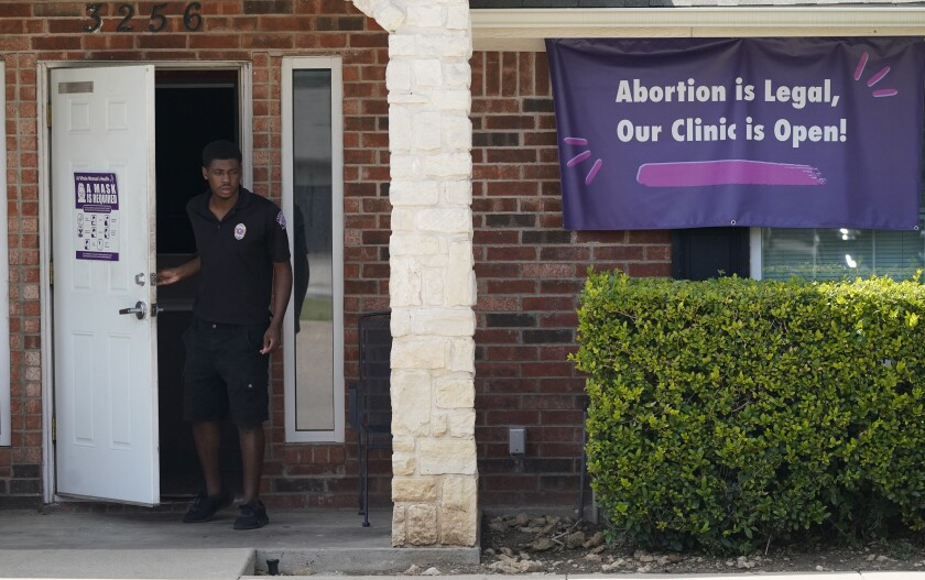 """A security guard outside a building with a banner reading, """"Abortion is legal, our clinic is open!"""""""