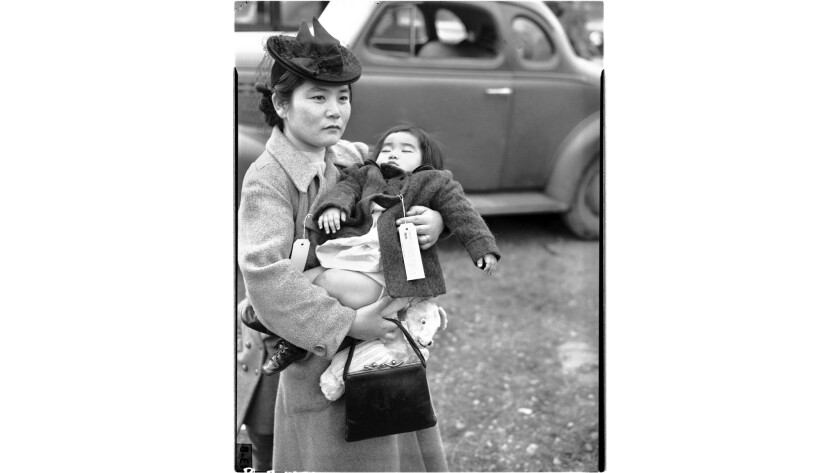 In a photo that became a symbol of a painful chapter in U.S. history, Fumiko Hayashida holds her sleeping daughter in March 1942 as they waited to be sent to an internment camp.