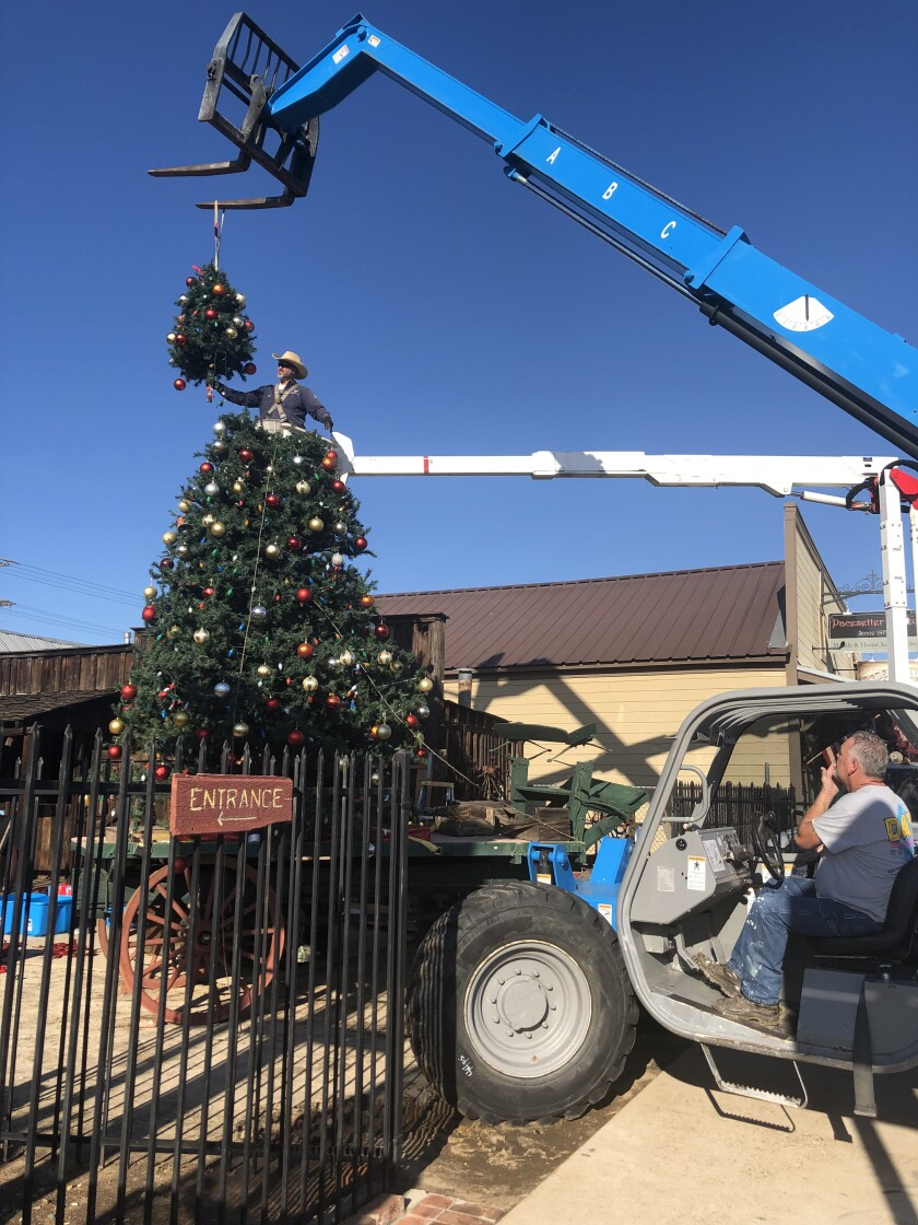The last section of the Ramona Christmas tree is carefully lowered into place.
