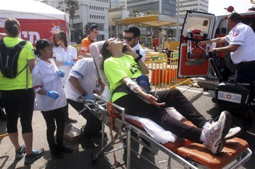 Paramedics treat a marathon runner suffering from heat In Tel Aviv, Israel, Friday, March 15, 2013. An Israeli soldier died of a heat stroke Friday after completing a half-marathon race in Tel Aviv, prompting Israel's minister of public security to criticize organizers for allowing the race to take