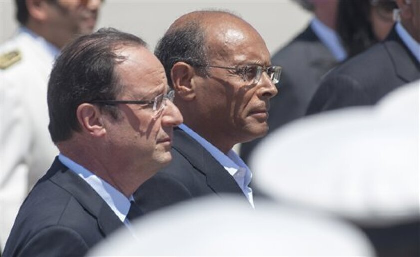 Tunisian President Moncef Marzouki, right, and French President Francois Hollande review the troops upon Hollande's arrival in Tunis, Thursday, July 4, 2013. French President Francois Hollande is making his first visit to Tunisia seeking a new page in relations with the North African country that was the birthplace of the Arab Spring pro-democracy uprisings. (AP Photo/Amine Landoulsi)