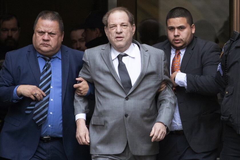 Men hold Harvey Weinstein's arms as he leaves court.