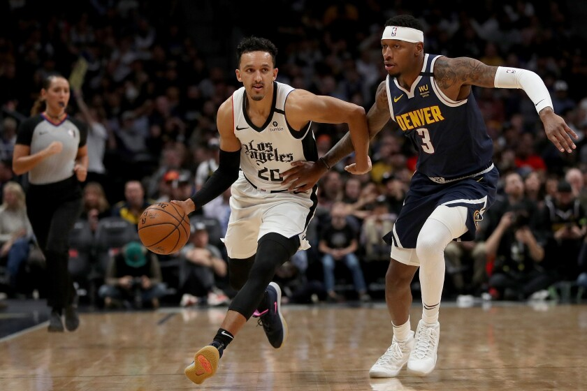 Clippers guard Landry Shamet brings the ball down the court against Denver's Torrey Craig on Sunday at Pepsi Center.
