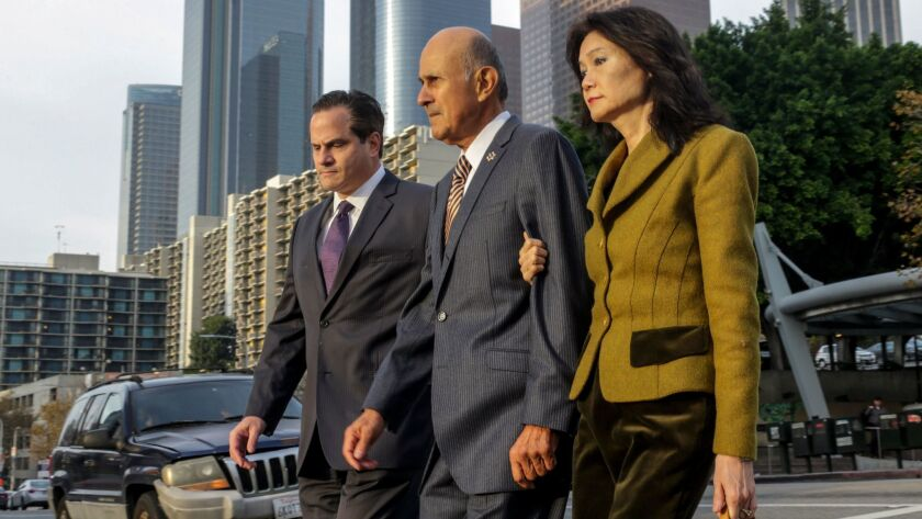Former Los Angeles County Sheriff Lee Baca, center, flanked by his attorney Nathan J. Hochman, left, and wife Carol Chiang, arrives at federal court.