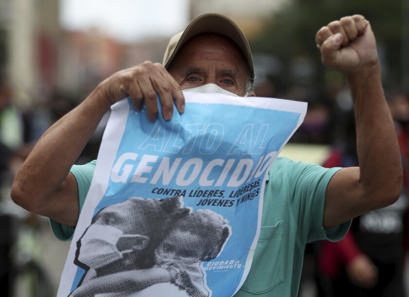 """A protester holds a poster with a message that reads in Spanish: """"Stop the Genocide,"""" during a demonstration against a wave of massacres, in Bogota, Colombia, Monday, Sept. 21, 2020. Rather than a national dispute between guerrillas and the state, violence in rural Colombia is now marked by a patchwork of local feuds between criminal groups who fight over drug routes, illegal mines and even gasoline smuggling routes. (AP Photo/Fernando Vergara)"""