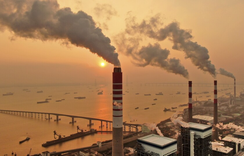 The sun sets near a coal-fired power plant on the Yangtze River in Nantong in eastern China's Jiangsu province on Dec. 12, 2018. Chinese power companies bid for credits to emit carbon dioxide and other climate-changing gases as trading on the first national carbon exchange began Friday, July 16, 2021 in a step meant to help curb worsening pollution. (Chinatopix via AP)