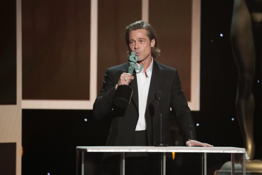 Brad Pitt gives the statue a peck as he accepts the 2020 SAG supporting actor award.