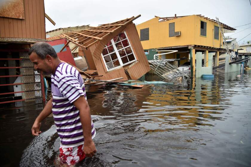 A man walks through flooded Juana Matos, Puerto Rico, after Hurricane Maria hit in September 2017.