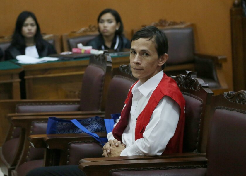 Indonesian teaching assistant Ferdinant Tjiong, sits on the defendant's chair prior to the start of his trial hearing at South Jakarta District Court in Jakarta, Indonesia, Thursday, April 2, 2015. An Indonesian court has sentenced a teaching assistant to 10 years in jail for sexually abusing three young children at a prestigious international school. (AP Photo/Tatan Syuflana)