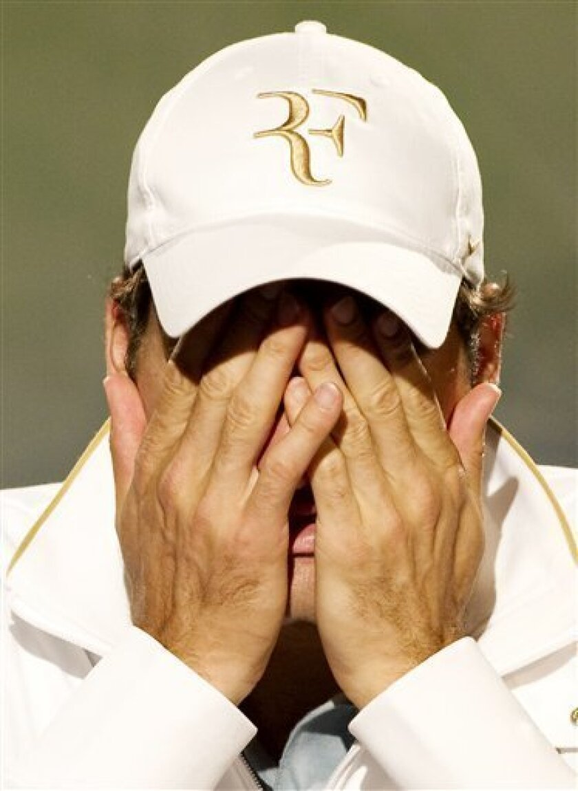 Defending champion Roger Federer covers his face during his press conference following his loss to Tomas Berdych of the Czech Republic, in their qurterfinal at the All England Lawn Tennis Championships at Wimbledon, Wednesday, June 30, 2010. (AP Photo/Tom Lovelock,AELTC, Pool)