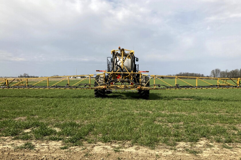 Farmer Rick Clifton drives a spray tractor across one of his fields.