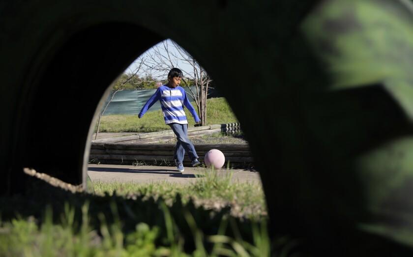A boy kicks a ball.