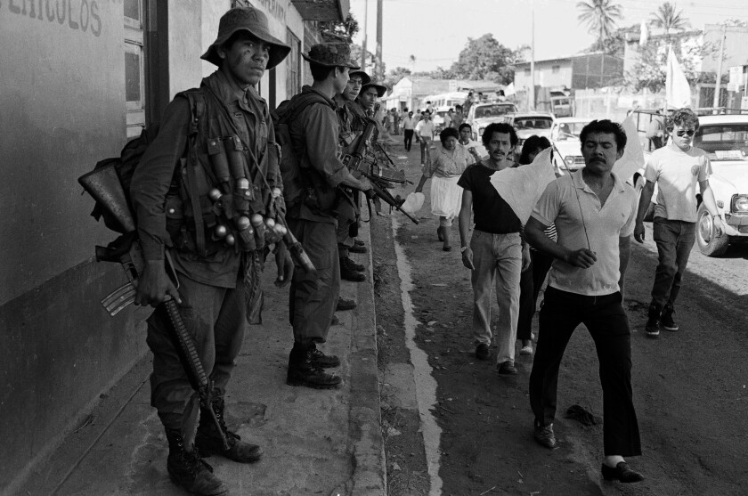 Salvadorans walk past troops in El Salvador in 1989.