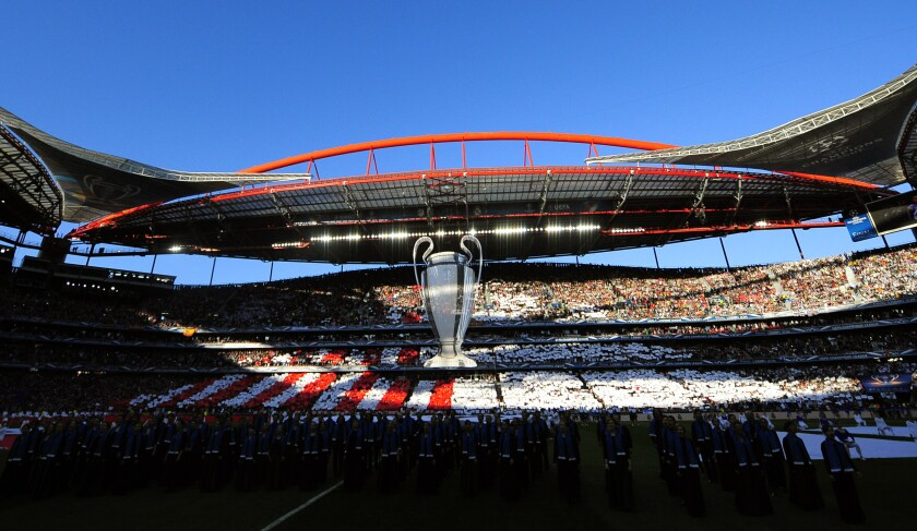 FILE - In this May 24, 2014 file photo, an image of the Champions League trophy is suspended from the roof of the stadium, ahead of the Champions League final soccer match between Atletico Madrid and Real Madrid, at the Luz stadium, in Lisbon, Portugal. UEFA announced Wednesday, June 17, 2020, that the Champions League will finish with a 12-day mini-tournament in Lisbon in August with the final match at the Luz stadium on Aug. 23. (AP Photo/Manu Fernandez)