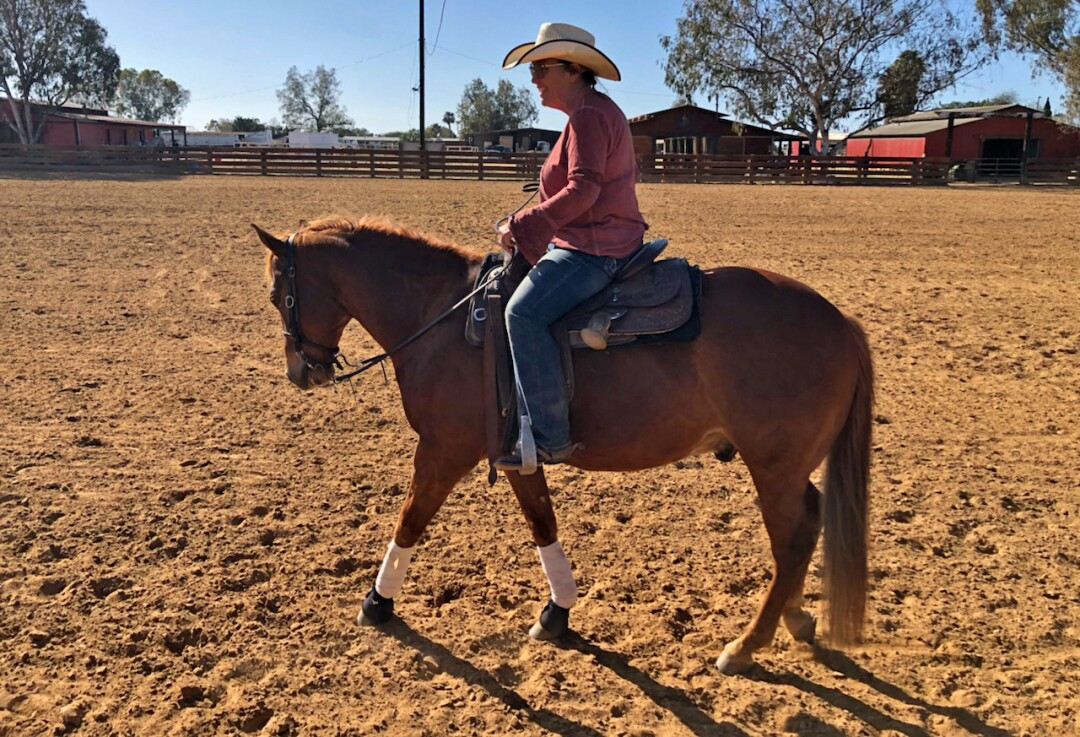 A person in a cowboy hat rides a horse in a large corral.
