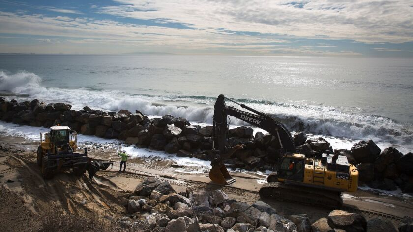 Caltrans contractor Nordic Industries works on constructing a rock barrier against erosion from tidal forces near Las Tunas Beach along Pacific Coast Highway in Malibu.
