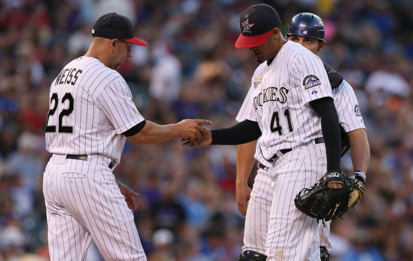 Colorado Rockies manager Walt Weiss, left, takes ball from starting pitcher Jair Jurrjens (41) as catcher Michael McKenry looks on in the fifth inning of a baseball game against the Los Angeles Dodgers in Denver, Friday, July 4, 2014. (AP Photo/David Zalubowski)