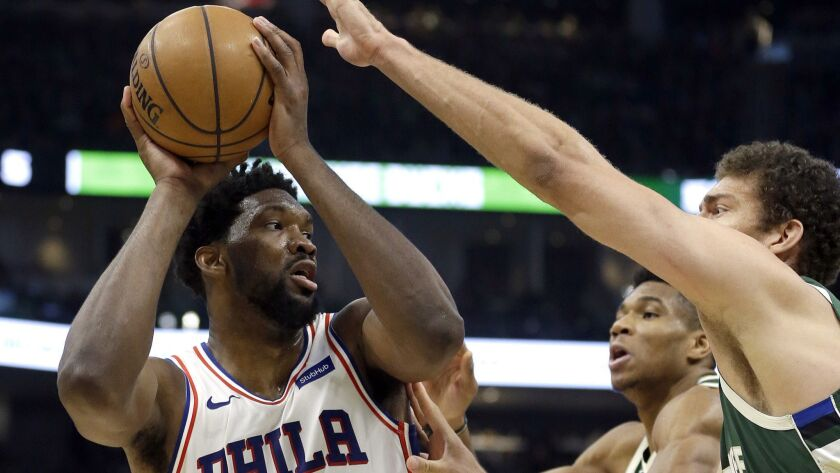76ers center Joel Embiid faces the double-team defense of Bucks forward Giannis Antetokounmpo and center Brook Lopez during the first half Sunday.