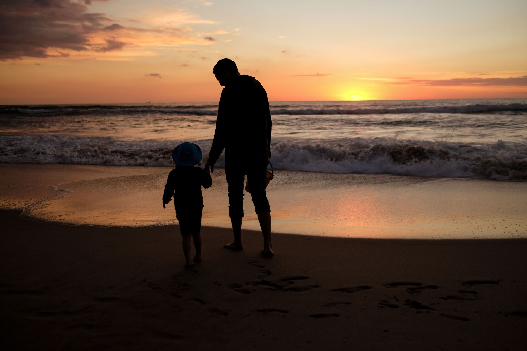 A dad and his daughter enjoy the last sunset of the year in Manhattan Beach, California, on December 31, 2018.