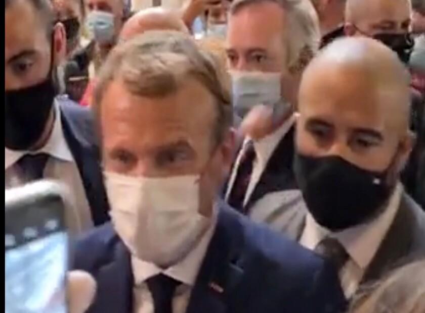 En esta imagen, tomada de un video proporcionado por Lyonmag.com, se muestra cómo un huevo lanzado al presidente de Francia, Emmanuel Macron (izquierda), le alcanza en el hombro izquierdo durante su visita a una feria de restauración en Lyon, Francia, el 27 de septiembre de 2021. (LYONMAG.COM vía AP)