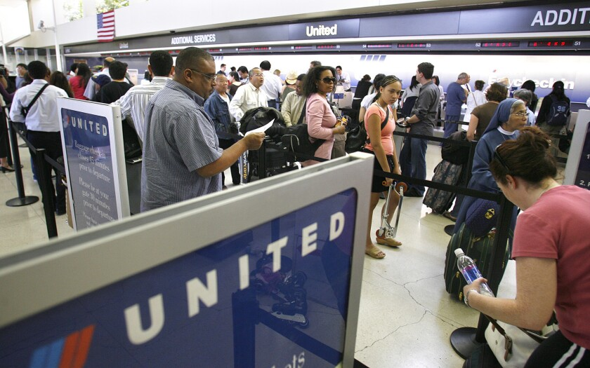 "Passengers wait in line to check in at the United terminal at LAX. United Airlines and Orbitz Worldwide have sued to stop a travel website from promoting ""hidden city"" booking."