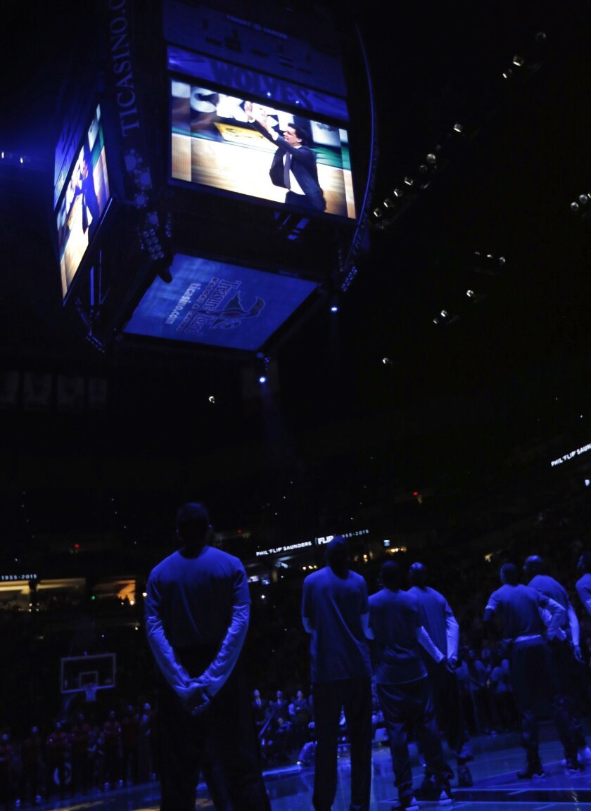 Minnesota Timberwolves players watch during a video tribute to honor head coach Flip Saunders, who died Oct. 25, 2015, prior to an NBA basketball game against the Portland Trail Blazers, Monday, Nov. 2, 2015, in Minneapolis. (AP Photo/Jim Mone)
