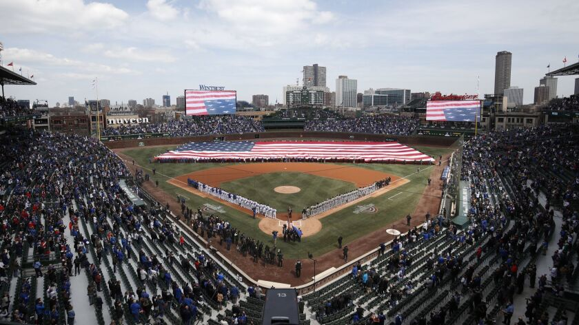 An American flag is unfurled in the outfield at Wrigley Field before the Chicago Cubs' home-opening