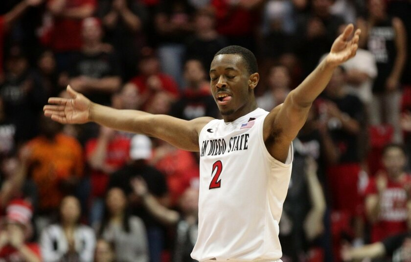 San Diego State point guard Xavier Thames, here exulting in an earlier win, likes to find ways to keep road crowds like Boise State's from rushing the court.