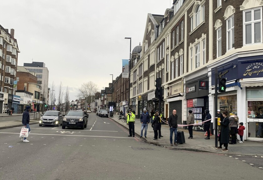 """Police attend the scene after an incident in Streatham, London, Sunday Feb. 2, 2020. London police say officers shot a man during a """"terrorism-related incident"""" that involved the stabbings of """"a number of people."""" (Isobel Frodsham/PA via AP)"""