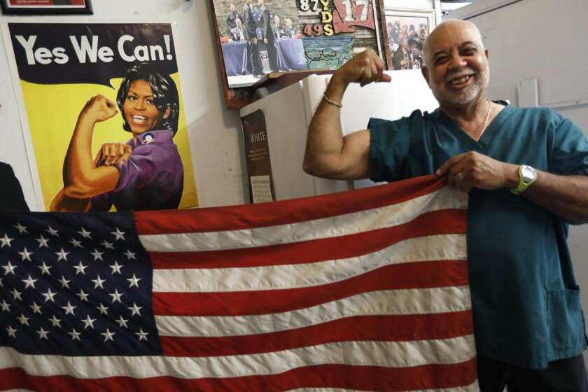Lawrence Tolliver with a poster of Michelle Obama as Rosie the Riveter