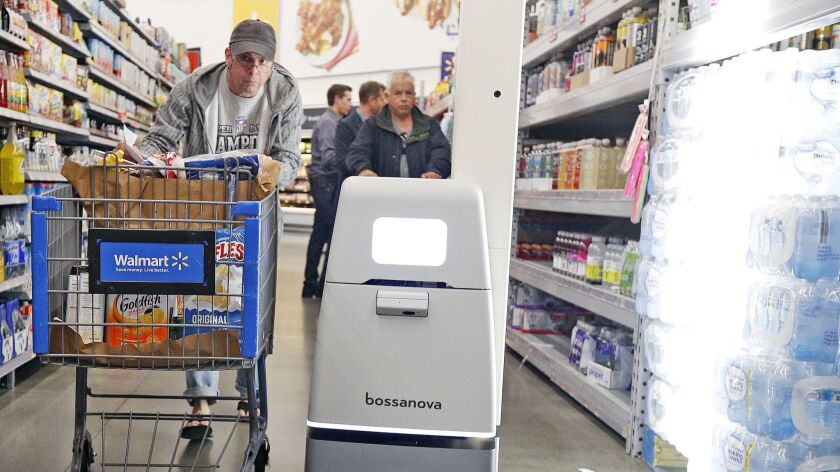 Michael Dimente, of North Hollywood, sneaks by a new Bossanova robot at Walmart in Burbank on Wednes