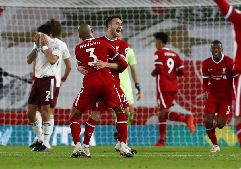 Diogo Jota (centro) celebra con Fabinho tras marcar el tercer gol de Liverpool en la victoria 3-1 ante Arsenal por la Liga Premier inglesa, el lunes 28 de septiembre de 2020, en Liverpool. (Jason Cairnduff/Pool vía AP)
