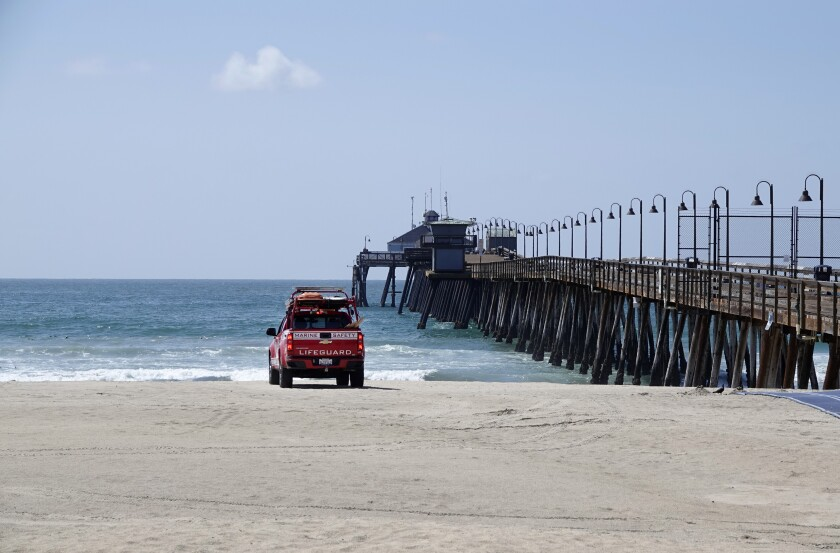 March 2020 file photo: Imperial Beach lifeguard patrols beach and pier, closed to the public due to the coronavirus pandemic.