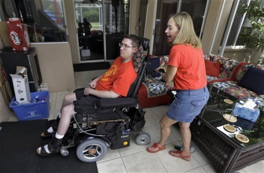 Chris Ott, right, helps her son, former Marine John Thomas Doody. J.T., who was shot while serving in Fallujah, Iraq., subsequently suffering an infection and a series of strokes that left him in a coma and relying on a ventilator to survive, Tuesday, Sept. 3, 2103, in Riverview, Fla. The Department of Veterans Affairs said Wednesday it supports expanding an enhanced caregivers benefit for grievously wounded veterans but only if Congress comes up with the billions needed to fund it. Congress cr
