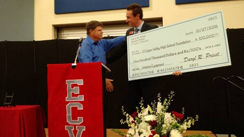 Local businessman Daryl Priest (left) presents a check for $100,000 to El Cajon Valley High School Vice Principal Jason Babineau for the Braves athletics program.