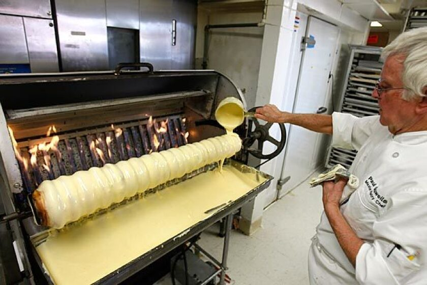 Paul Gauweiler ladles batter on the spindle of his baumkuchen machine at his Huntington Beach bakery. It's one of the few such ovens in the U.S.