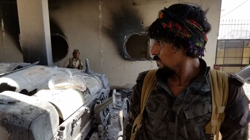 A Syrian Democratic Forces fighter at an outpost in east Raqqah surveys damage wrought by Islamic St