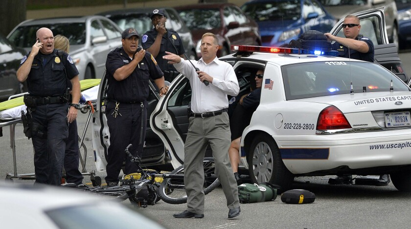 Police officers attend to an officer in a cruiser that was wrecked after shots fired were reported near the U.S. Capitol in Washington.