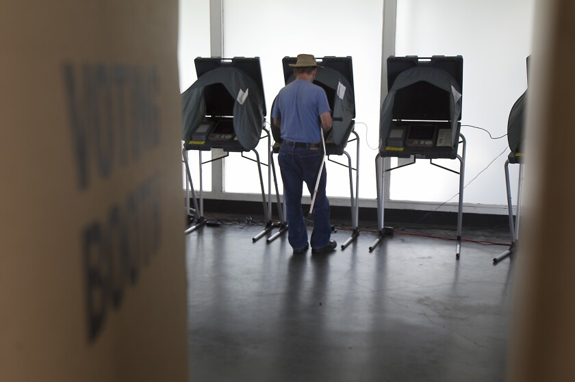 A voter casts a ballot at the Royal Palm Fire Station in Costa Mesa in 2015.