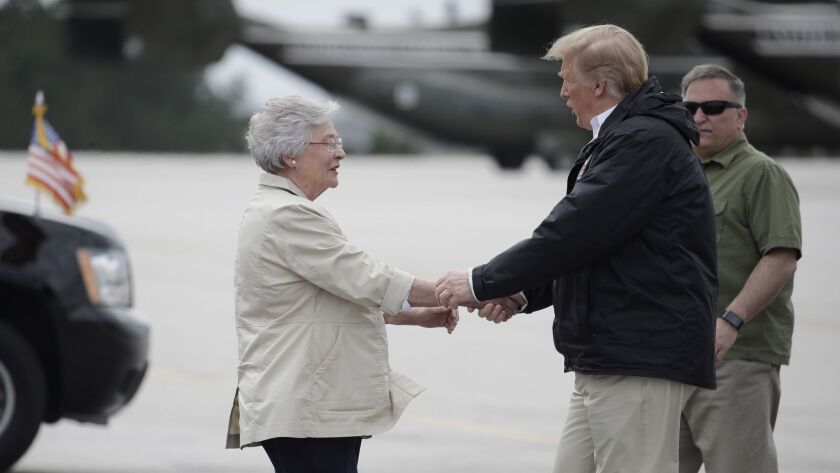 President Trump is greeted by Gov. Kay Ivey in Auburn, Ala., en route to Lee County, where a tornado killed 23 people.