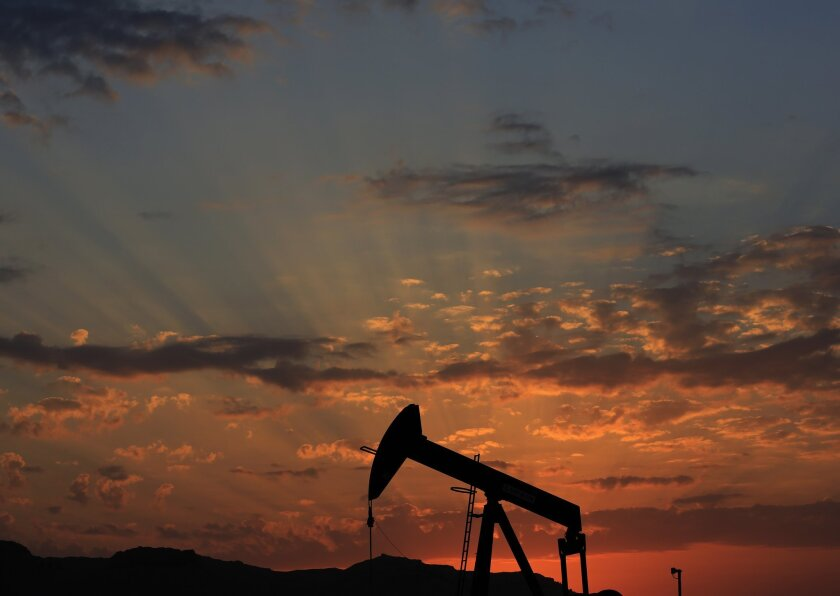 An oil pump at sunset in the desert oil fields of Sakhir, Bahrain on Dec. 13. Gasoline prices remain low in the United States and are expected to soon drop below $2 a gallon.